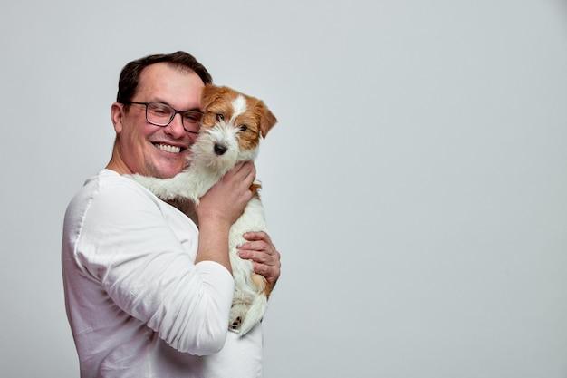 O cachorro deita no ombro de seu dono