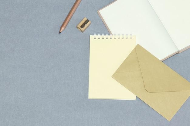 O caderno aberto, envelope, lápis de madeira e apontador no plano de fundo cinzento