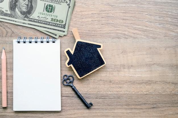 O caderno em branco da vista superior, o dinheiro e a casa de madeira modelam para o conceito dos bens imobiliários.
