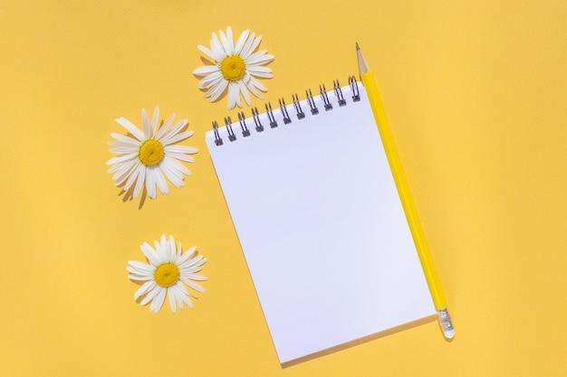 O caderno em uma espiral com uma folha vazia, um lápis amarelo e margarida floresce em um fundo amarelo brilhante.