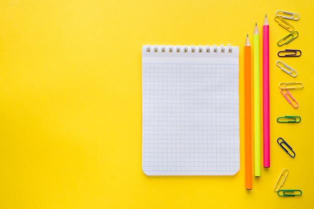 O caderno, lápis colore clipes de papel no amarelo. copyspace
