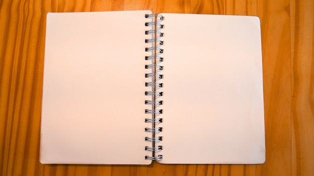 O caderno na tabela de madeira na cafetaria.