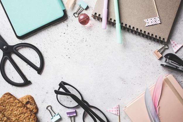 O caderno, os vidros, as penas e os artigos de papelaria objeta em um fundo cinzento, vista superior.