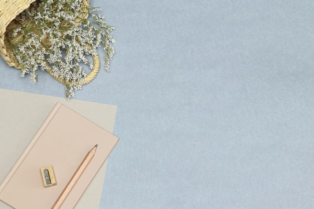 O caderno rosa, lápis de madeira e apontador, cesta com flores na mesa azul