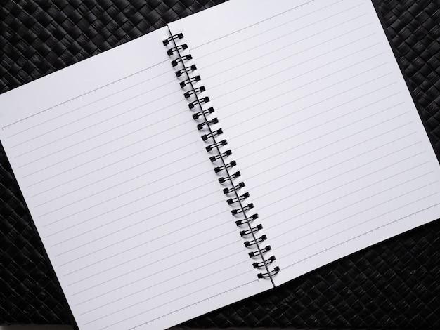 O caderno tem uma página de papel branco na caixa preta.