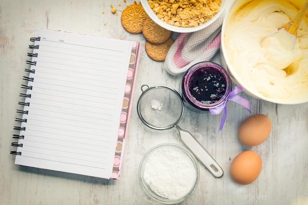 O caderno vazio da receita com os ingredientes do bolo de queijo preparou-se sobre um fundo de madeira branco.
