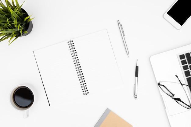 O caderno vazio está sobre a tabela branca da mesa de escritório com portátil, copo de café e materiais de escritório.