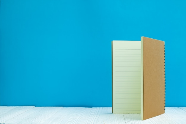 O caderno vazio no fundo azul da parede da parte dianteira de madeira branca da tabela com espaço da cópia para adiciona o texto ou a palavra da propaganda.