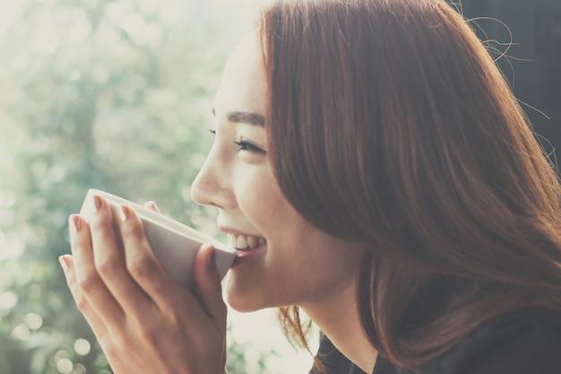 O café bebendo da mulher em uma cafetaria, secretárias está feliz quando bebem o café.