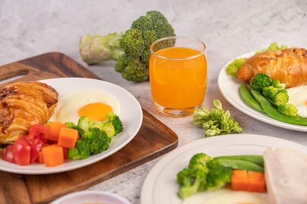 O café da manhã consiste em frango, ovos fritos, brócolis, cenoura, tomate e alface em um prato branco.
