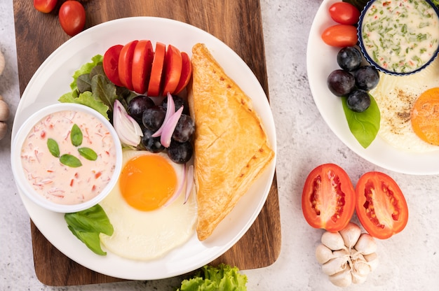 O café da manhã consiste em pão, ovo frito, molho para salada, uvas pretas, tomate e cebola fatiada.