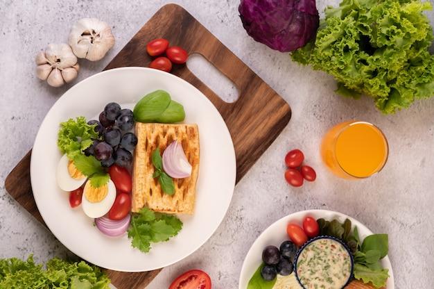 O café da manhã consiste em pão, ovos cozidos, molho para salada de uva preta, tomate e cebola fatiada.