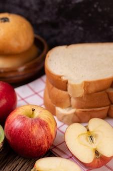 O café da manhã é composto por pão, maçãs, uvas e kiwi em uma mesa de madeira