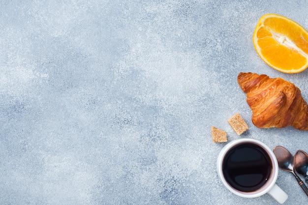 O café da manhã é uma xícara de café com croissant e laranja. copie o espaço