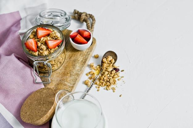O café da manhã inclui granola orgânica, morangos e iogurte.