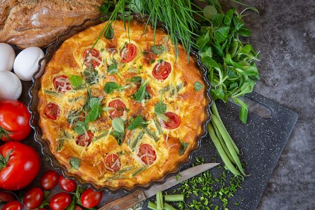 O café da manhã no domingo de manhã. omelete no forno com feijão verde, tomate, ervas e queijo.