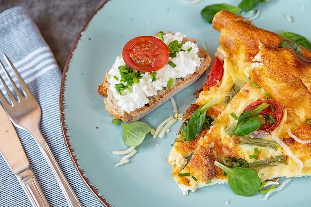 O café da manhã no domingo de manhã. pedaços de omelete com pão em um prato em fatias. omelete no forno com feijão verde, tomate, ervas e queijo.