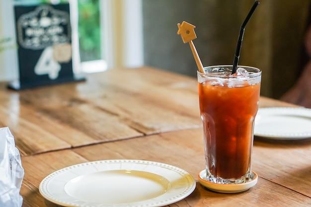 O café de gelo e um prato são colocados em uma tabela de madeira.