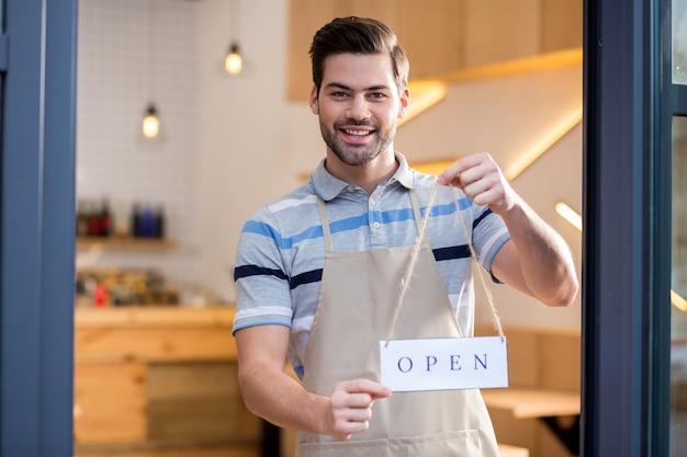 O café está aberto. homem simpático e simpático, segurando uma etiqueta e convidando para um café na porta