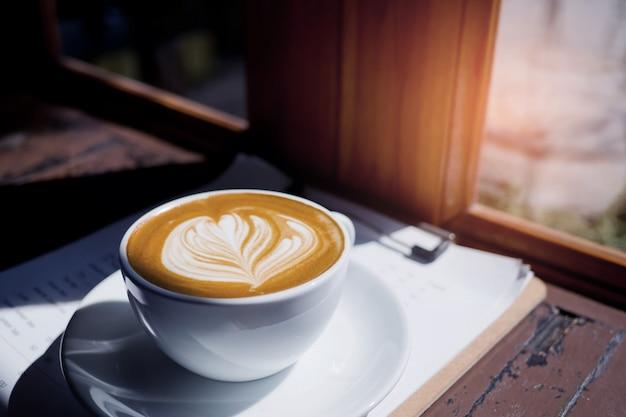 O café quente da arte do latte na tabela de madeira, relaxa o tempo