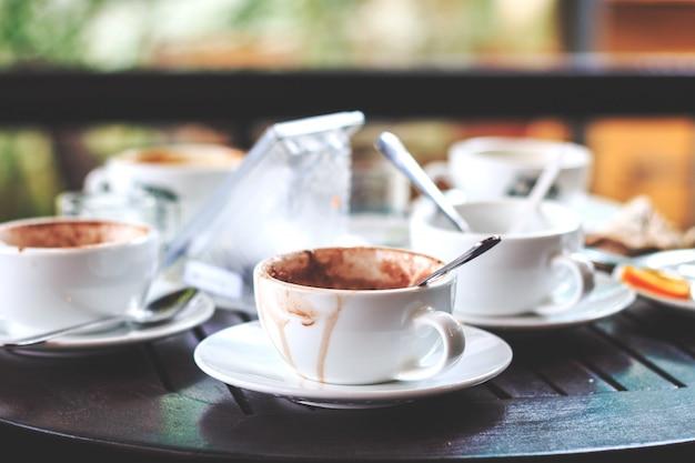 O café quente em um copo é bebido na tabela com foco macio e sobre a luz no fundo