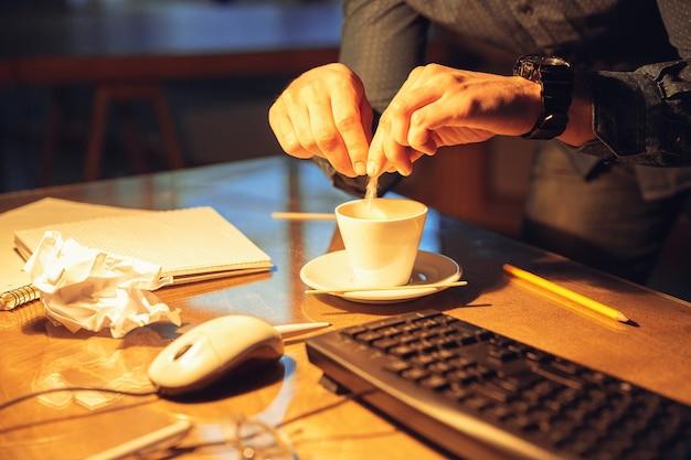 O café resgata. homem trabalhando sozinho no escritório durante a quarentena do coronavírus ou covid-19, permanecendo até tarde da noite. jovem empresário, gerente fazendo tarefas com smartphone, laptop, tablet no espaço de trabalho vazio.