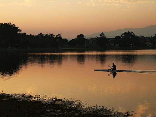 O caiaque de treinamento de homem navega no pôr do sol do rio