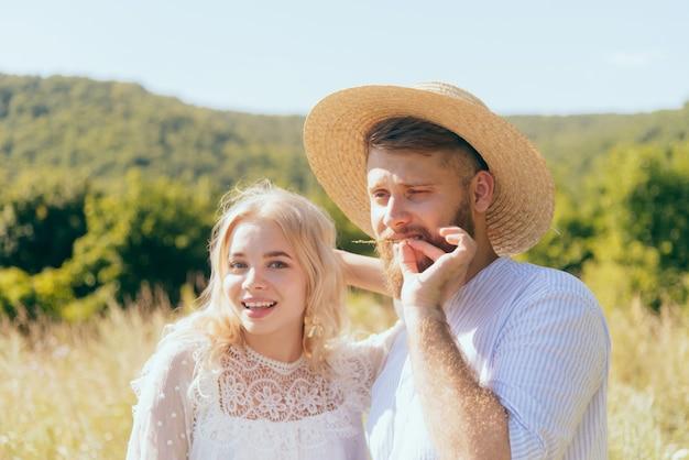 O caipira feliz com um chapéu fica com sua namorada amada em um dia ensolarado de verão