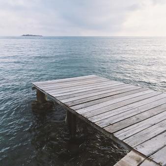 O cais de madeira com mar azul antes do pôr do sol. beleza da natureza. conceito de férias.