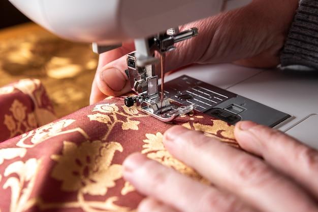 O calcador da máquina de costura com agulha costura tecido vermelho com flores.