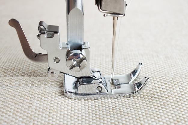 O calcador de máquina de costura moderna faz uma costura em tecido biege. processo de costura