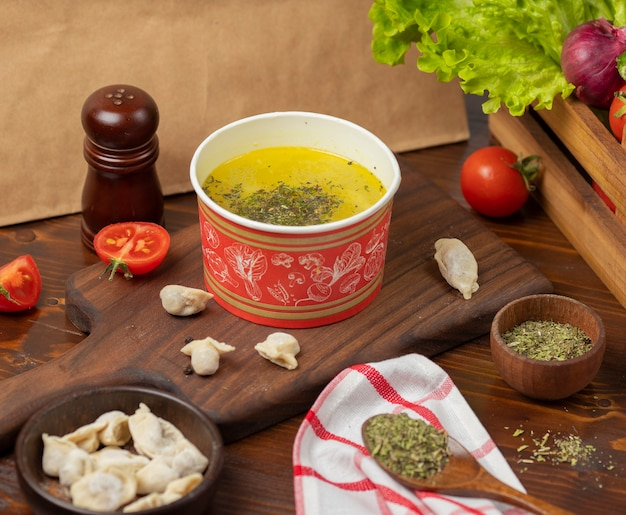 O caldo de galinha com sopa das ervas na bacia descartável do copo serviu com vegetais verdes.