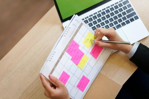 O calendário da verificação da mulher de negócios tem o plano no conceito do planeamento do memorando, do trabalho e da agenda.