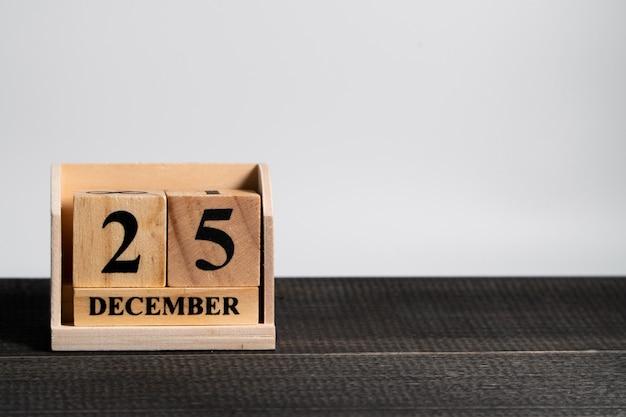 O calendário de bloco de madeira ajustou-se no natal data o 25 de dezembro no fundo de madeira preto.
