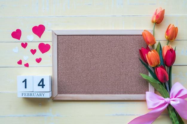 O calendário de madeira em 14 de fevereiro é composto de flores e corações