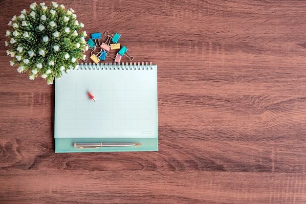 O calendário em branco da vista superior com uma caneta na mesa de escritório para a composição do espaço de cópia