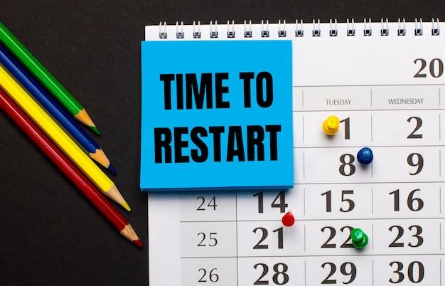 O calendário tem papel azul claro com o texto hora para reiniciar. lápis de cor próximos em uma superfície escura. vista de cima.