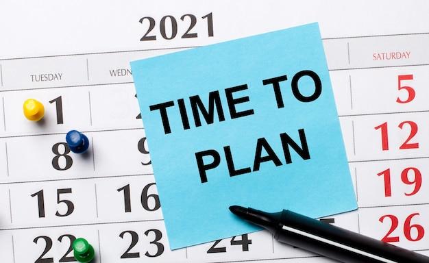 O calendário tem um adesivo azul com o texto hora de planejar e um marcador preto. conceito organizacional. vista de cima