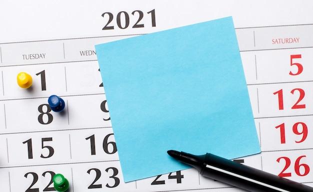 O calendário tem um adesivo azul e um marcador preto. conceito organizacional. vista superior com espaço de cópia