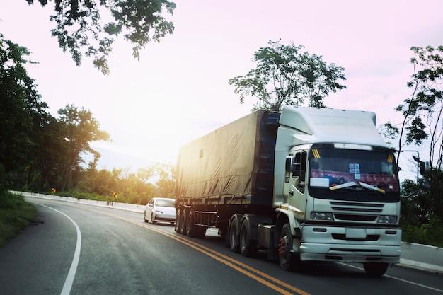 O caminhão segue na estrada sinuosa pela paisagem da floresta do pôr do sol.