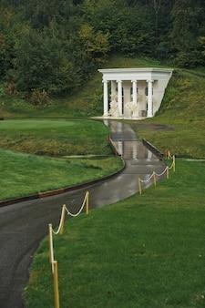 O caminho leva ao edifício branco na colina verde