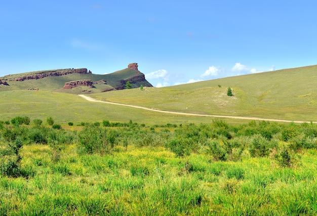 O caminho que sobe a colina até o penhasco rochoso no verão sob o céu azul. sibéria, rússia