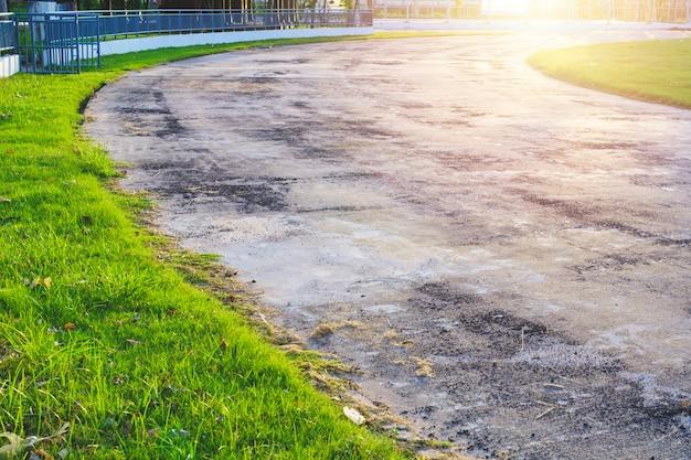 O caminho velho e as árvores bonitas seguem para a corrida ou o passeio e o ciclismo relaxam no parque.