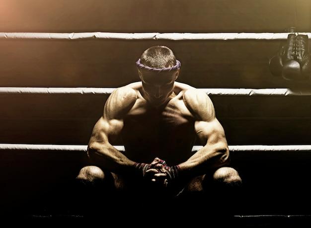 O campeão mundial de boxe tailandês está sentado no ringue e se preparando para a próxima luta. o conceito de esporte, estilo de vida saudável, nutrição esportiva. mídia mista