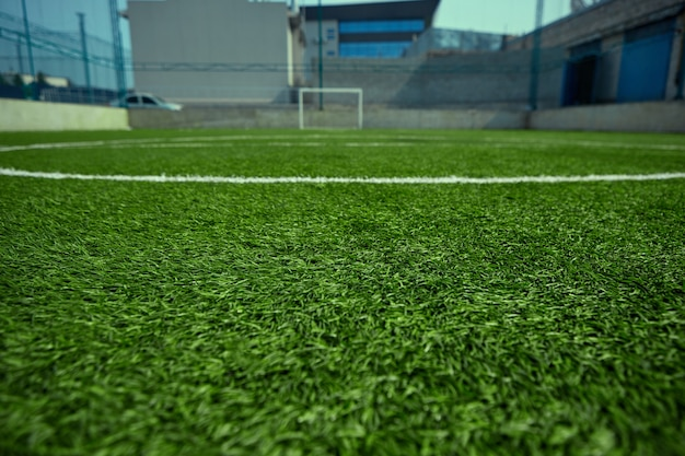 O campo de futebol vazio e grama verde