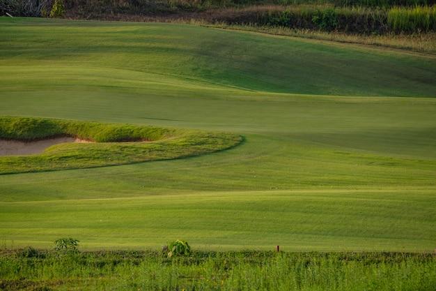 O campo de golfe bonito, o depósito da areia e o fundo da grama verde.