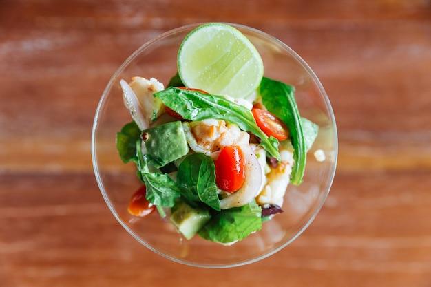 O canape picante e azedo do estilo tailandês da lagosta serviu uma parcela no vidro de vinho.