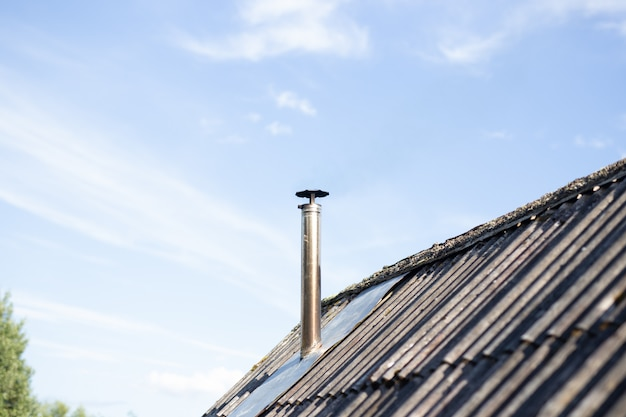 O cano no telhado. chaminé. casa de campo. a casa com uma chaminé. céu azul.