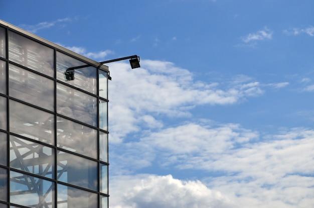 O canto do edifício de escritórios envidraçado com a lâmpada de rua moderna embutida