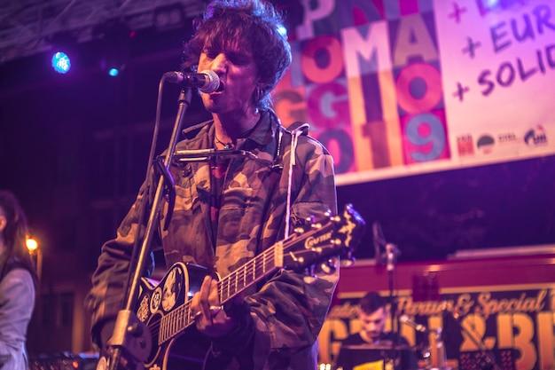 O cantor de rock em destaque canta com ênfase enquanto suas expressões faciais se tornam aparentes